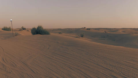 Low altitude aerial view of a recreational desert camp in the evening, UAE Live Action
