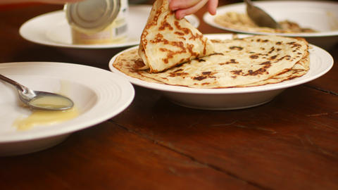 A stack of pancakes in a plate on the table Live Action