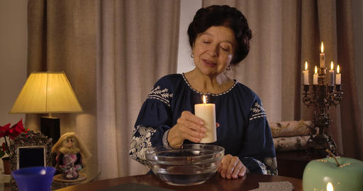 Mature Caucasian woman holding big candle and moving it around plate with water Live Action