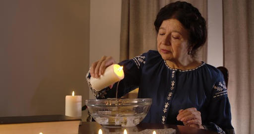 Close-up of mature Caucasian woman pouring candle wax into water. Serious female Live Action
