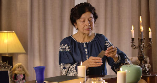 Portrait of Caucasian mature woman sitting at the table and reading cards Live Action