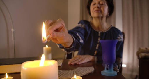 Close-up of female Caucasian hand lighting up candle standing at the foreground Live Action