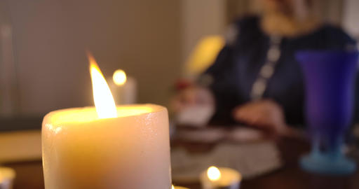 Close-up of lighting candle standing on the table as blurred Caucasian woman Live Action