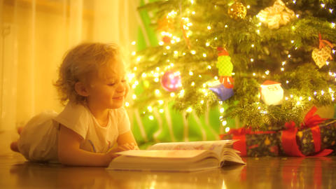 Happy blonde baby girl looks at pictures in a fairytale book near decorated Live Action