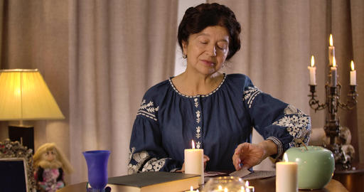 Cheerful Caucasian old woman with black hair and brown eyes reading cards and Live Action