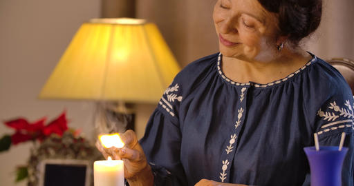 Smiling Caucasian female magician lighting up candles with match. Camera moving Live Action