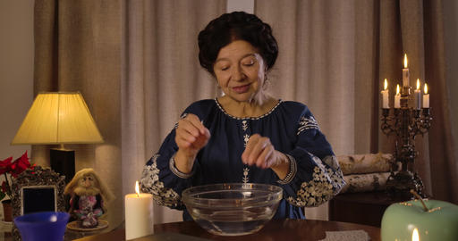 Old Caucasian brunette woman putting lighting candle on the table and moistening Live Action