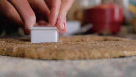 Woman hands cutting cookies on whole wheat dough on floured countertop Live Action