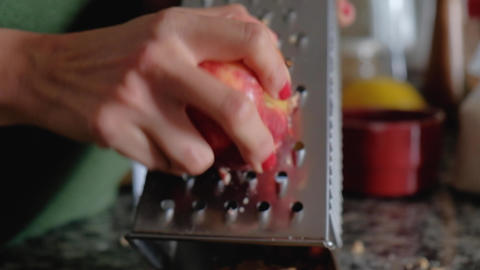 Close up of woman hands grating a red apple with skin on a metallic grater Live Action