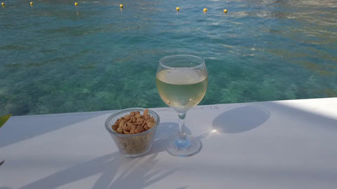 Glass of white wine on the table near sea Live Action