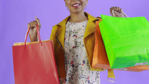 Portrait of african american woman with shopping bags on purple Background in Live Action