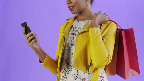 Portrait of african american woman with shopping bags and mobile phone on purple Live Action