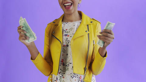 Attractive Afro american woman is counting money against a purple background Live Action