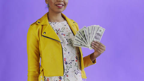 Portrait of african american woman with money fan on purple Background in Studio Live Action