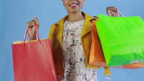Portrait of african american woman with shopping bags on blue Background in Live Action