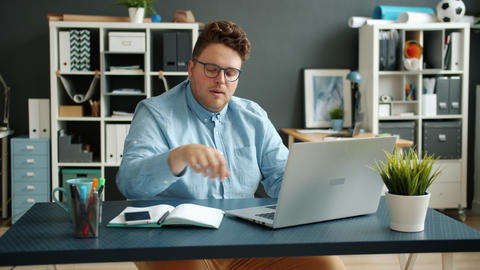 Serious businessperson handsome guy typing using laptop computer indoors in Live Action