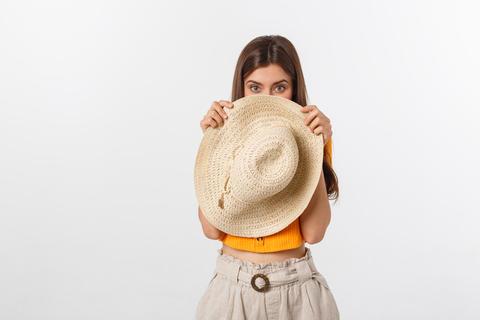 Flirty funky caucasian woman hiding behind fashionable trendy red head wear Fotografía