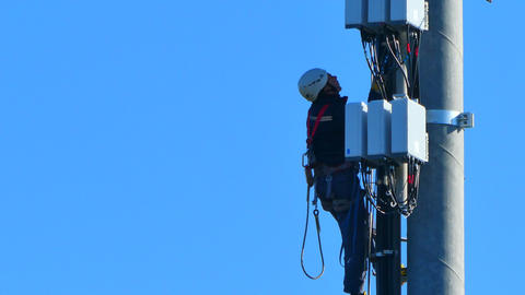 workers working on an antenna Live Action