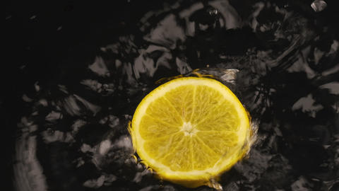 Ripe, juicy orange slice falls on a black surface covered with water. Slow Live Action