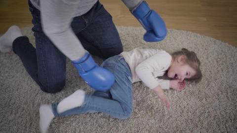 Top view of cheerful Caucasian man boxing little laughing girl. Laughing father Live Action