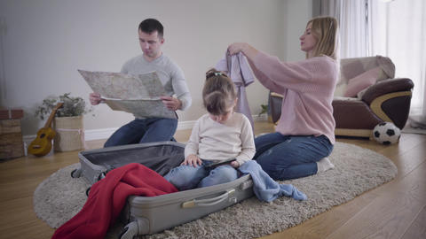 Young Caucasian family packing suitcase before trip. Man looking at map, woman Live Action