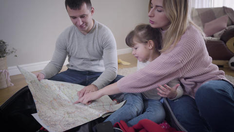 Portrait of happy young Caucasian family making route for future trip. Smiling Live Action