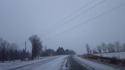 Driving Uphill Around Road Bend During Winter Snow Storm in Day. Driver Point of View POV Snowing Live Action