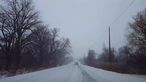 Driving Behind Vehicle on Rural Road While Snow Storm. Driver Point of View POV Rear of Truck Live Action