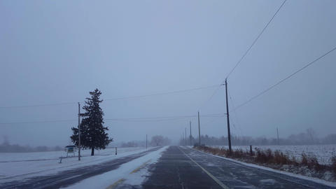 Driving Winter Snow Storm on Rural Road in Day. Driver Point of View POV Snowing Blizzard Snowfall Live Action