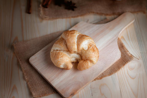 Croissant on wooden cut board on table wood and fabric select fo フォト