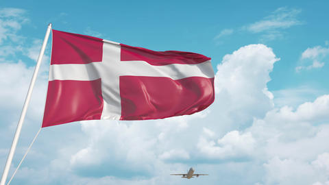 Commercial airplane landing behind the Danish national flag. Tourism in Denmark Live Action