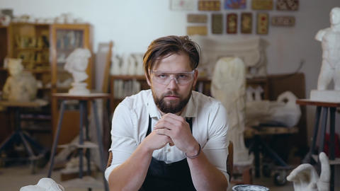 Attractive concentrated young modern bearded master in special glasses looking Live Action