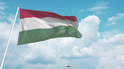 Commercial airplane landing behind the Hungarian national flag. Tourism in Live Action