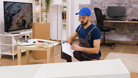 Young male worker assembly details of furniture in new home Live Action