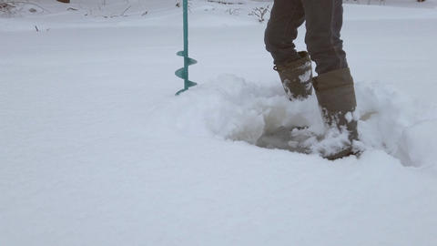 Man in winter boots clears the ice from the snow and drills ice with a drill for Live Action
