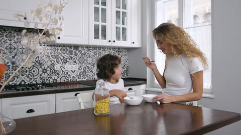 Young mother with 5-aged child eating healthy breakfast in the home kitchen Live Action