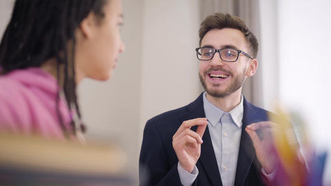Close-up portrait of handsome Caucasian tutor teaching language to African Live Action