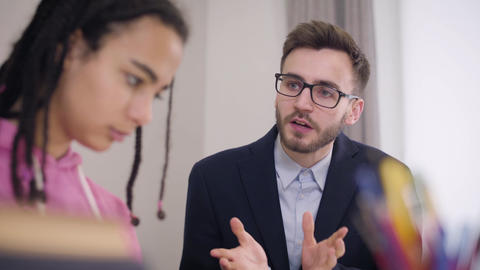Close-up of strict male Caucasian teacher scolding young African American Live Action