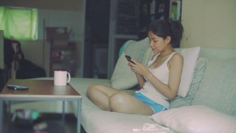 Young Asian Woman is chatting on phone sitting on sofa at home Live Action