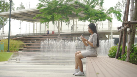 Attractive Asian Woman digital artist is drawing in park with fountains Live Action