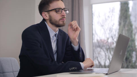 Young tired Caucasian businessman holding head with hand and typing on laptop Live Action