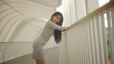 Young Asian Woman with long black hair in pedestrian bridge Live Action