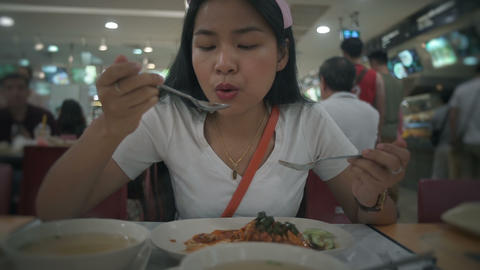 Young Thai Woman eating on a food court Live Action