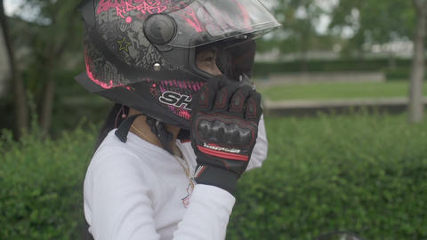 SAMUT PRAKAN, THAILAND - AUGUST 24, 2019: Portrait of Young Thai Woman wearing motorcycle helmet Live Action