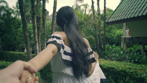 Thai Girl walking and holding her boyfriend's hand at tropical garden Live Action