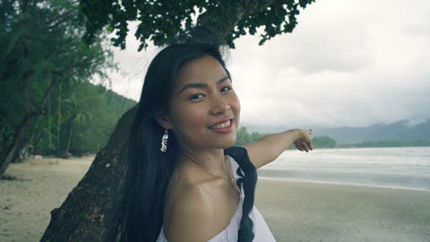 Cute smiling Girl at beach is pointing her finger on mountains Live Action
