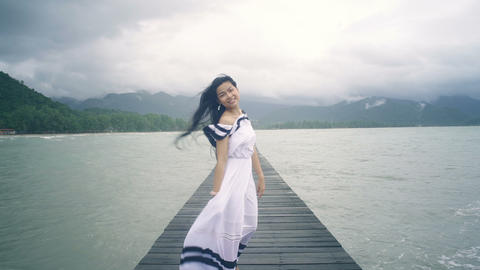 Thai Girl in white dress walking on wooden pier to camera Live Action