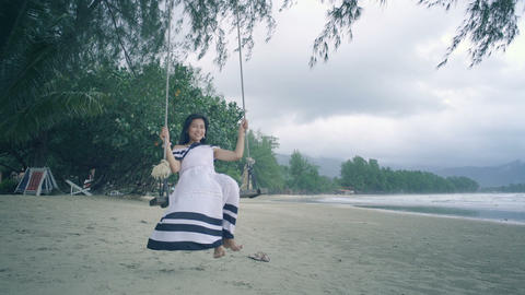 Girl in white dress swinging on a swing at beach Live Action