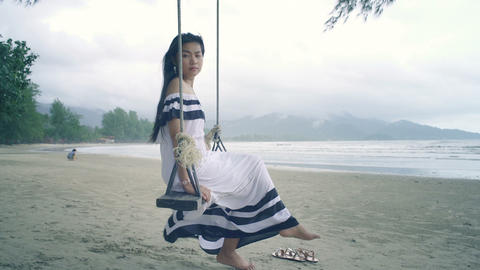 Young Woman in white dress sitting on a swing at beach Live Action