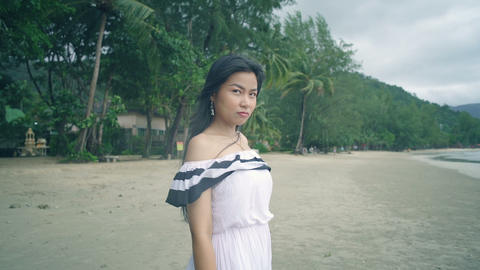 Thai Girl with pouting face at beach looking on camera Live Action